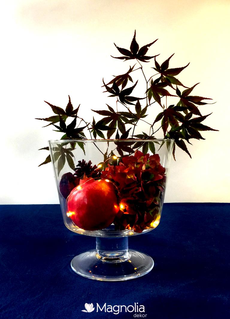 Herbstliche Tischdeko in einer mit Granatapfel, Hortensien und roten Ahorn