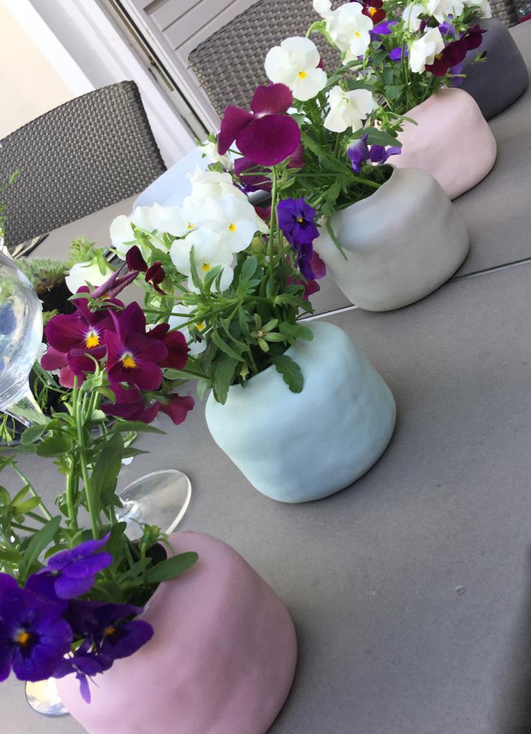 Windlichter, umfunktioniert zu kleinen Vasen, gefüllt mit Stiefmütterchen