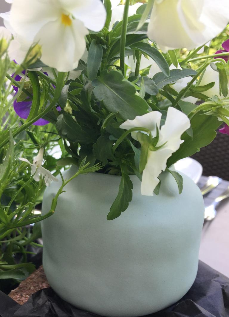 Windlichter aus Porzellan als kleine Vasen mit Steifmütterchen