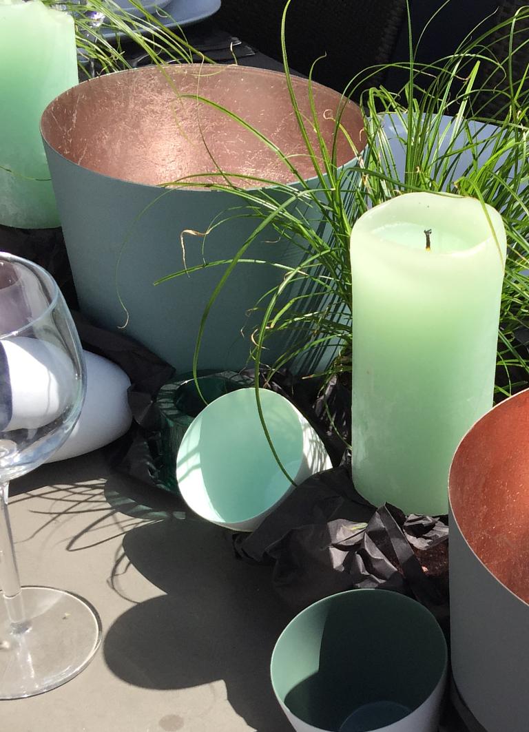 Windlichter in verschiedenen Größen und frisches Grün für den Gartentisch