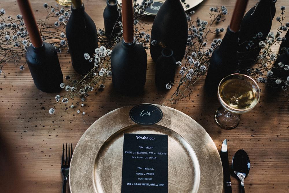 Rustikale Tischdeko mit goldenen Platzteller - schwarze Flaschen